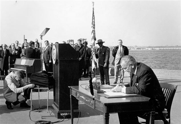 President Lyndon B. Johnson signing the 1965 Immigration Act on Liberty Island in New York City.